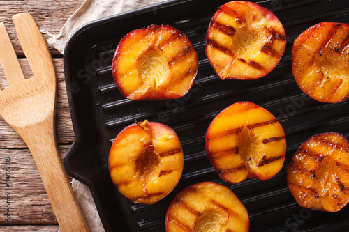 Ripe peaches on a a grill pan close-up. horizontal top view