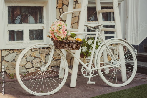 white vintage bicycle with a wedding bouquet in a basket