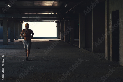 Fotografia  Male athlete running on industrial building, fitness