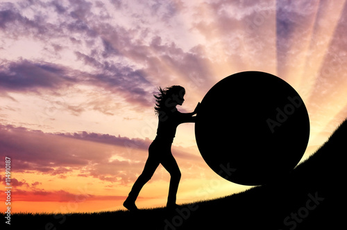Fotografía  Silhouette of a strong woman pushing a stone up.