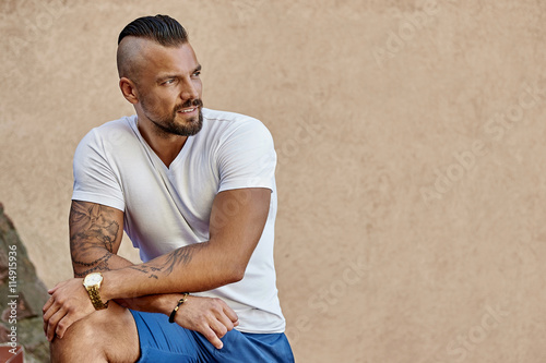 fototapeta na szkło Tattooed brutal man with arms folded wearing white t-shirt - cop