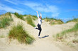 junge Frau springt in den Dünen an der Nordsee