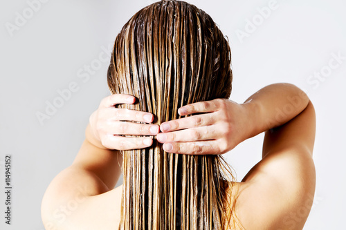 Photo  Woman applying hair conditioner. Isolated on white.