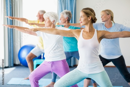 Fotografie, Tablou  Instructor performing yoga with seniors