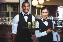 Mixed Race Waiter And Waitress Holding A Serving Tray