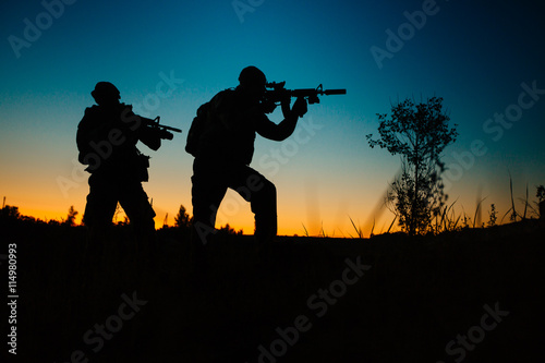 Foto op Canvas Militair Silhouette of military soldiers with weapons at night. military concept.