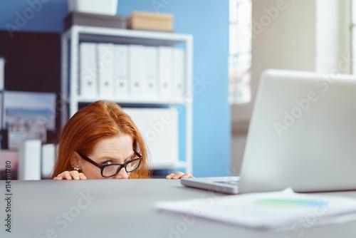 Fotografía  frau im büro versteckt sich unter dem schreibtisch
