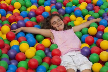 Fototapeta na wymiar Girl lie down in a colorful plastic ball pool