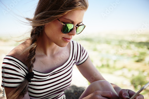 obraz PCV Close-up of beautiful young female in stylish sunglasses texting message on her smart phone. Pretty woman networking outdoors in summer day.