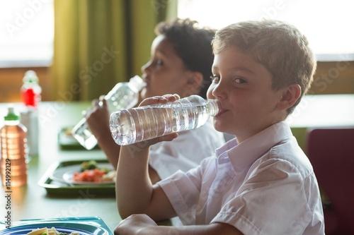 Portrait of schoolboy drinking water from bottle