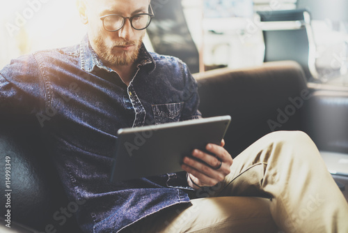 Bearded Hipster working tablet computer modern Interior Design Loft Office.Man relax Vintage sofa use contemporary device Hand.Blurred Background.Creative Business Startup Idea.Closeup.Film effect.