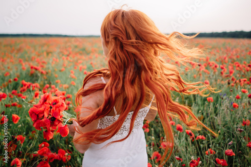 Fotografía  Beautiful young red-haired woman in poppy field with flying hair