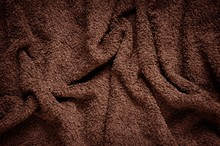 Furry Wrinkled Blanket Texture. Close-up Of Brown Material, May Be Used As Background.