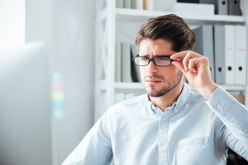 Close-up portrait of businessman in eyeglasses looking at monitor