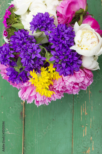 obraz lub plakat bouquet of colorful flowers on green wooden planks