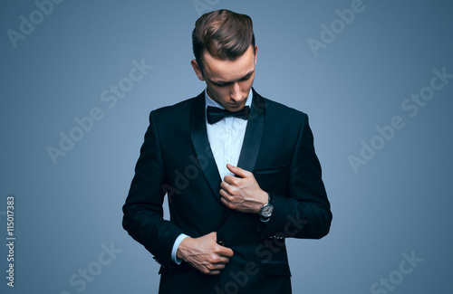 Fototapeta Handsome young man in a tuxedo looking at the camera