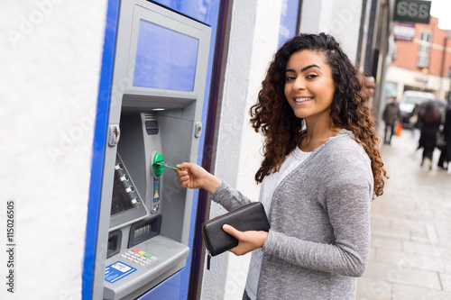 Obraz na plátne young woman at the cash machine