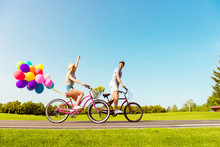 Two Lovers Riding Bicycles With Balloons On The Background Of Sk