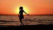 The girl dances on the beach at sunset. Slow motion