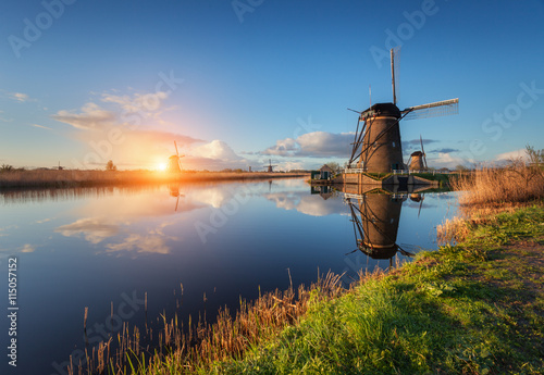 fototapeta na ścianę Beautiful traditional dutch windmills near the water channels with reflection in water at colorful sunrise in famous Kinderdijk, Netherlands