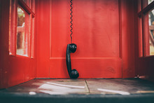Black Handset Hanging In A Red Telephone Box. Telephone Receiver Hanging Touching The Floor In A Red Call Telephone Booth. The Concept Of Technological Progress And The Development Of Communication