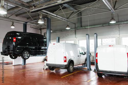 Fotografie, Obraz  SUV big service station, black minibus raised up on lift