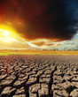 low dark clouds in sunset and drought earth closeup