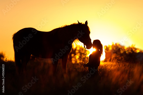 Beautiful silhuette of girl and horse at sunset