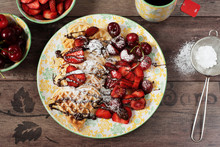 Soft Belgian Heart Shaped Waffles With Cherries And Strawberries, Chocolate Topping And Powdered Sugar On Yellow Plate. Black Tea, Berries And Powdered Sugar. Wooden Background, Top View, Close Up