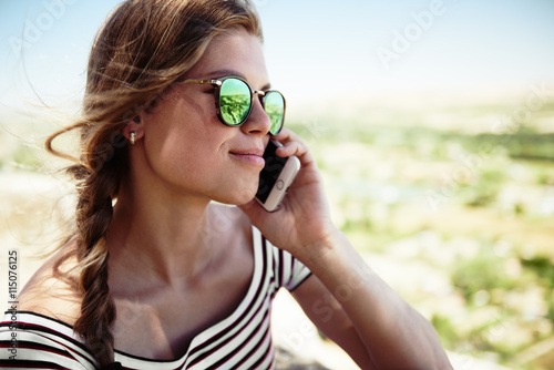 obraz dibond Fashion girl with mobile phone on the nature. Young attractive woman talking on telephone.