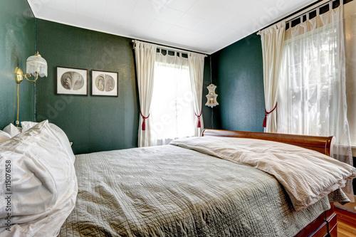 Fotografie, Obraz  Small bedroom with wooden bed, dark green walls