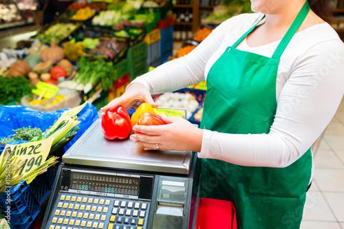 Tableau sur Toile Verkäuferin wiegt Gemüse auf Waage im Laden