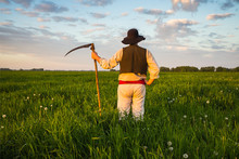 Man In Old Clothes Mows Grass