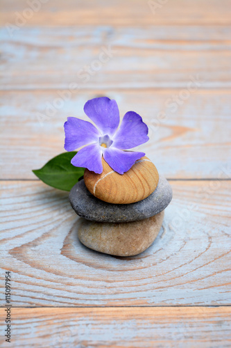 Fotografia  Three cairn natural Zen stones piled up on a old brown gray wooden background wi