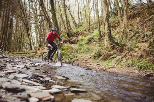 Foto op Canvas Bossen Mountain biker in stream at forest