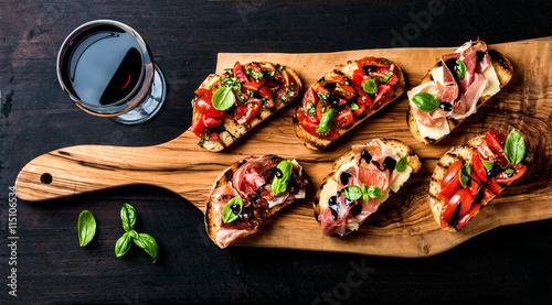 Obraz na plátně Brushetta set and glass of red wine