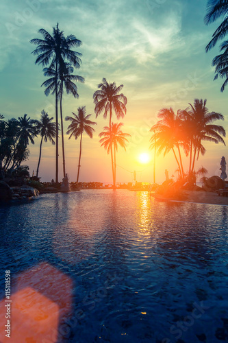 Foto op Aluminium Bomen Tropical sunset and silhouettes of palm trees on sea beach.