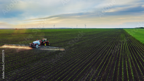 Valokuva  Tractor spraying field at spring