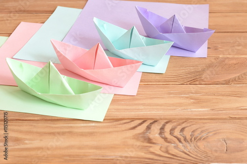 Four Colored Origami Boats Toys On A Wooden Table Square Sheets Of