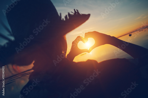 Woman In Straw Hat Making Heart Symbol With Her Hands At Sunset At