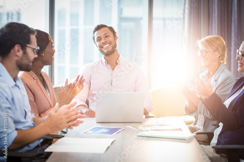 Coworkers applauding a colleague after presentation Canvas Print