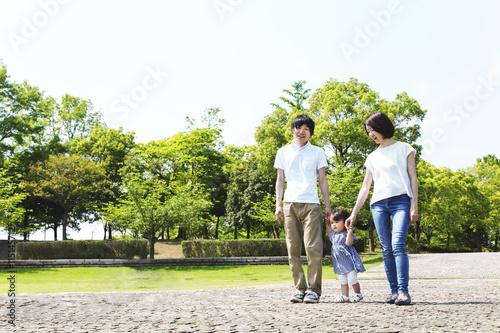 公園の石畳を散歩する幼い女の子と父母