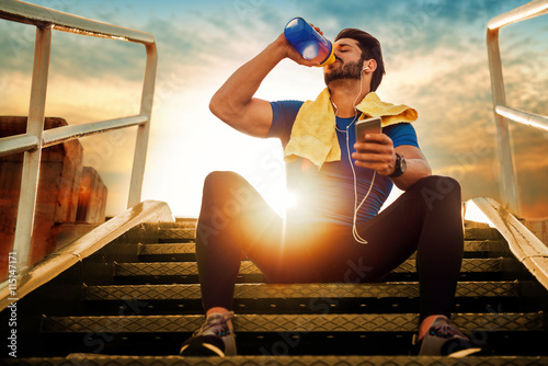 Fotografia  Young athlete man drinking protein cocktail