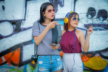 Fashion Lifestyle, Beautiful Two Young Woman.  With Abstract Graffiti Art. ,And Fashion Sunglasses.