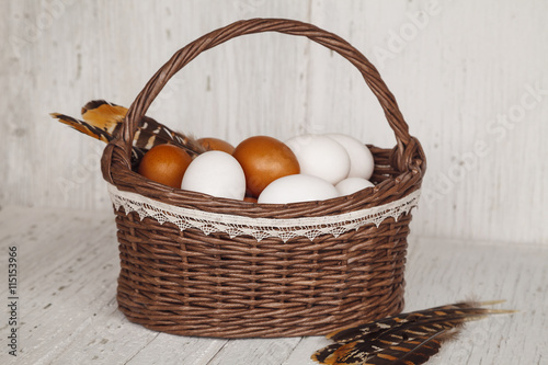 Wicker brown basket with eggs and feathers in cousy background Canvas Print