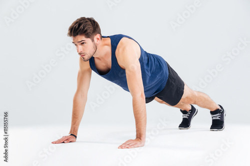 Fotografía  Concentrated young sportsman exercising and doing push ups