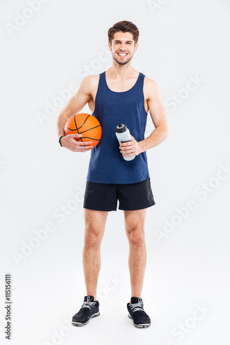 Photo  Smiling young sportsman holding basket ball and water bottle