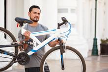 Male Cyclist Lifting A Bike In...