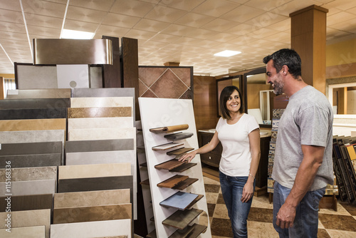 Fotografía  Smiling couple choosing tile in home decoration store