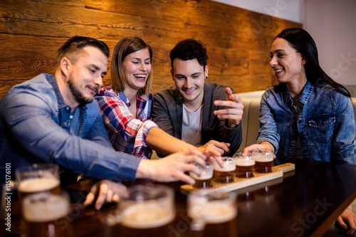 Foto  Friends enjoying beer at table
